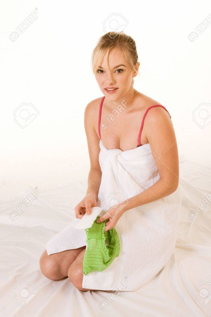 Blonde female holding feminine hygienic pad, preparing to stick it to her green panties Stock Photo - 4151667