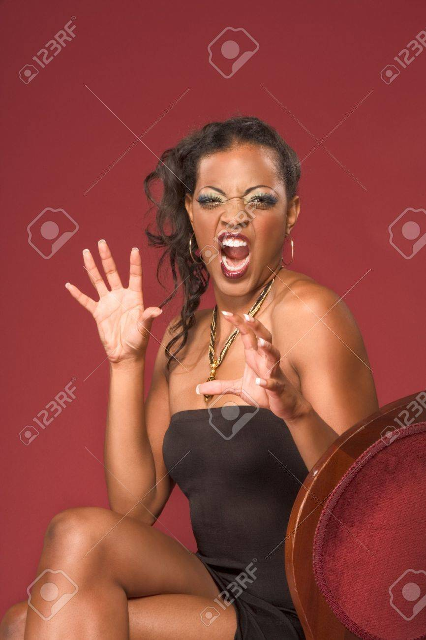 Crazy screaming glamour young dark skinned biracial mulatto female with dramatic makeup wearing jewelry necklace sitting on red chair Stock Photo - 4259220