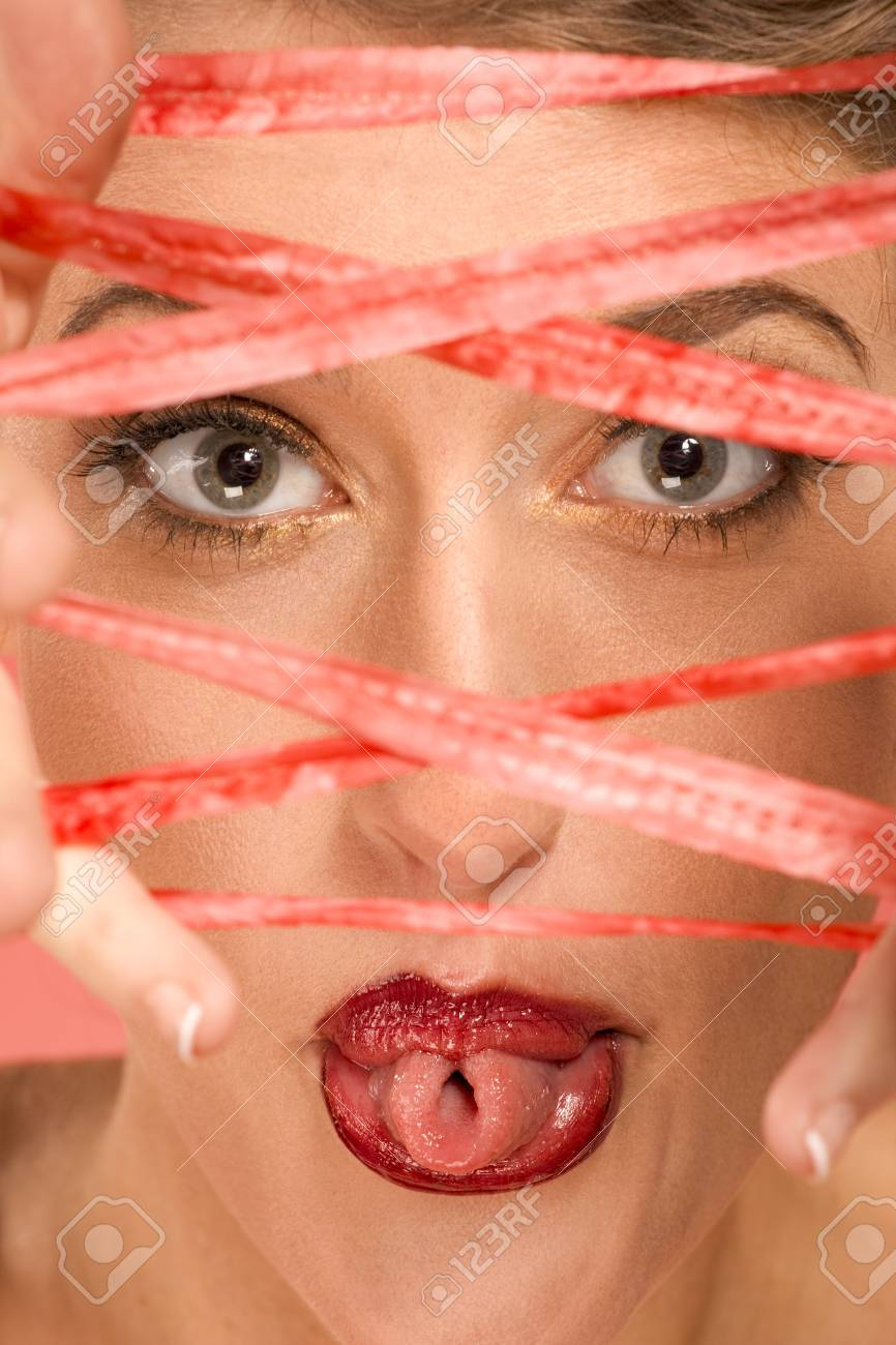 Portrait of beautiful woman wearing dramatic makeup, sticking out her tongue and rolling it into tube shape, looking through rope stretched over her fingers Stock Photo - 4389843