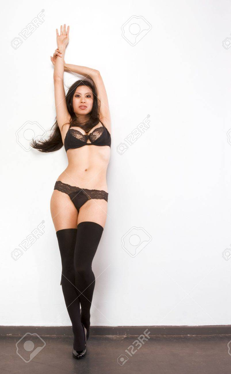 Young Chinese female fashion model in thigh high stockings and black lingerie standing by wall with arms raised Stock Photo - 5319884