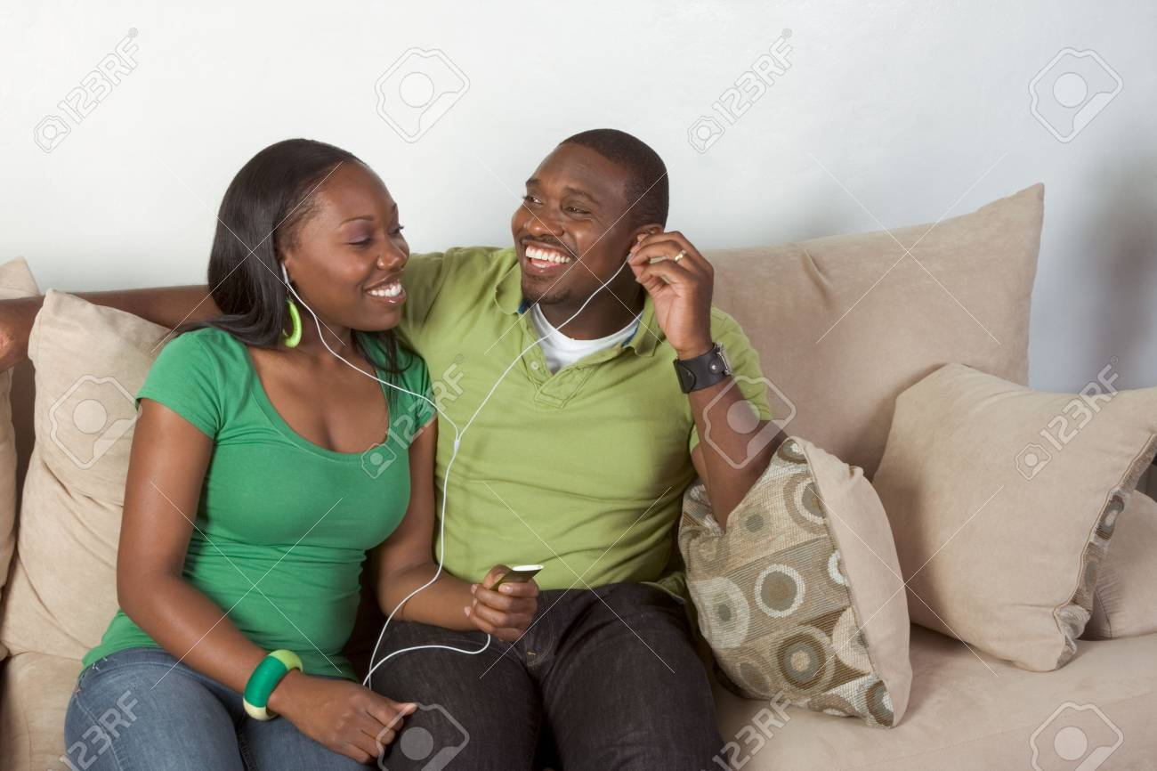 Young African American couple sitting in living room on couch enjoying time together and share usage of portable MP3 player, using the same headphones Stock Photo - 5941287