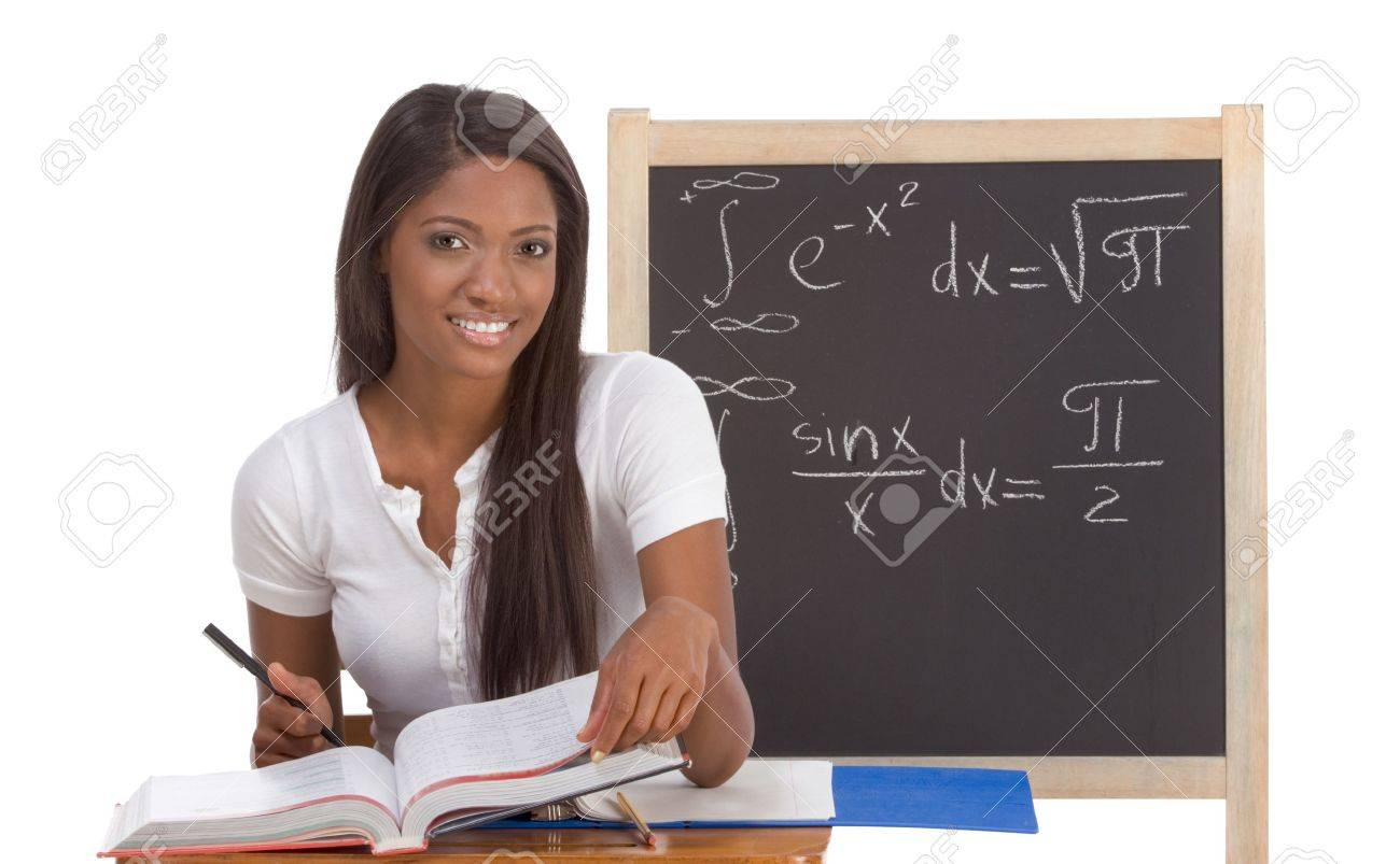 High school or college ethnic African-American female student sitting by the desk at math class. Blackboard with advanced mathematical formals is visible in background Stock Photo - 6080303