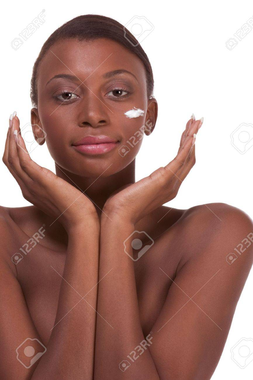 Skincare - Young naked ethnic African-American woman with slicked back hair applying cream moisturizer on her face after sauna Stock Photo - 6080267