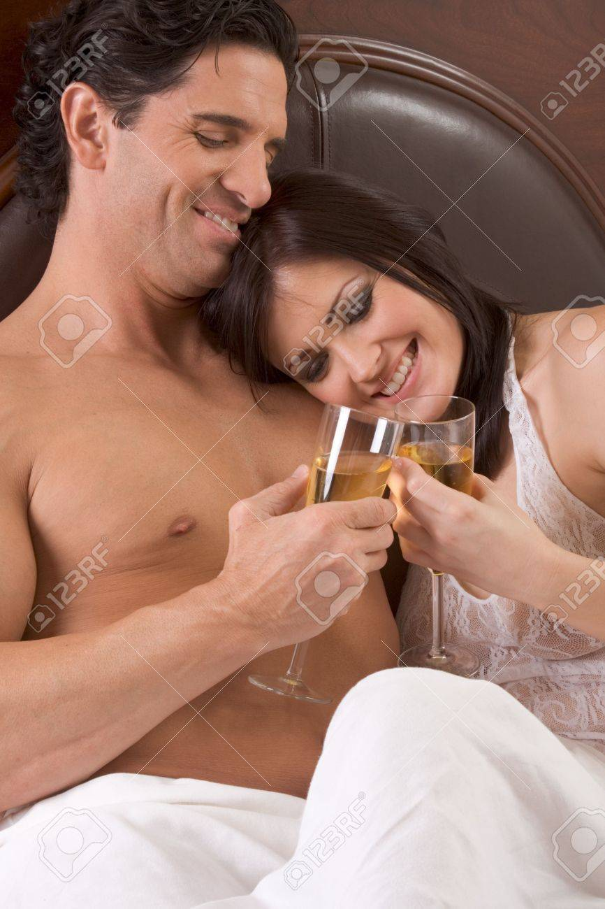 Young sexy heterosexual couple celebrating with wine in bed Stock Photo - 6559565