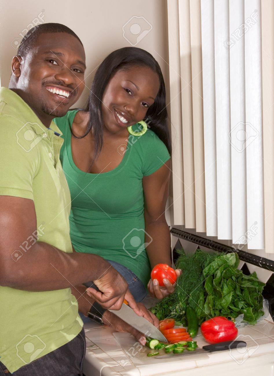 Young black African American couple preparing vegetable salad on kitchen countertop Stock Photo - 9498538
