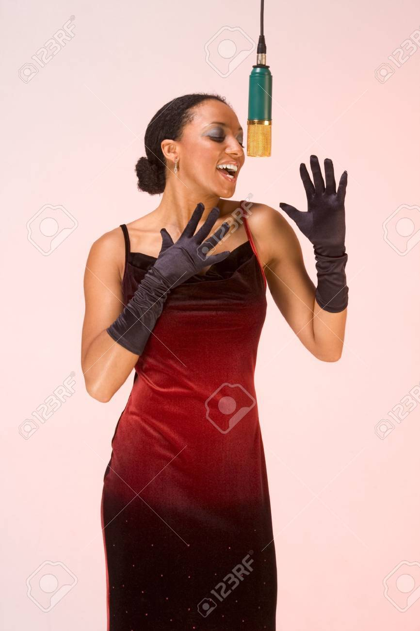 dark skinned sexy female in red concert dress and black gloves sings by microphone Stock Photo - 10277649