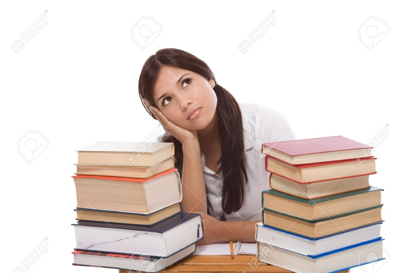 bored High school or college Latina female student sitting by the desk with pile of books in front of her Stock Photo - 12460897
