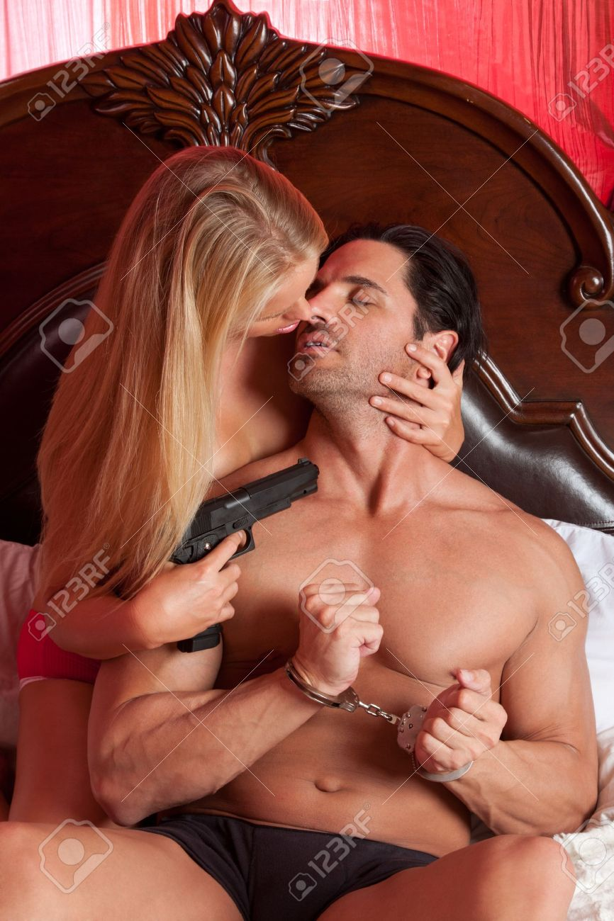 Lovers - sensual couple making love in bed. Mystery woman in lingerie holding gun, man in handcuffs Stock Photo - 14172479