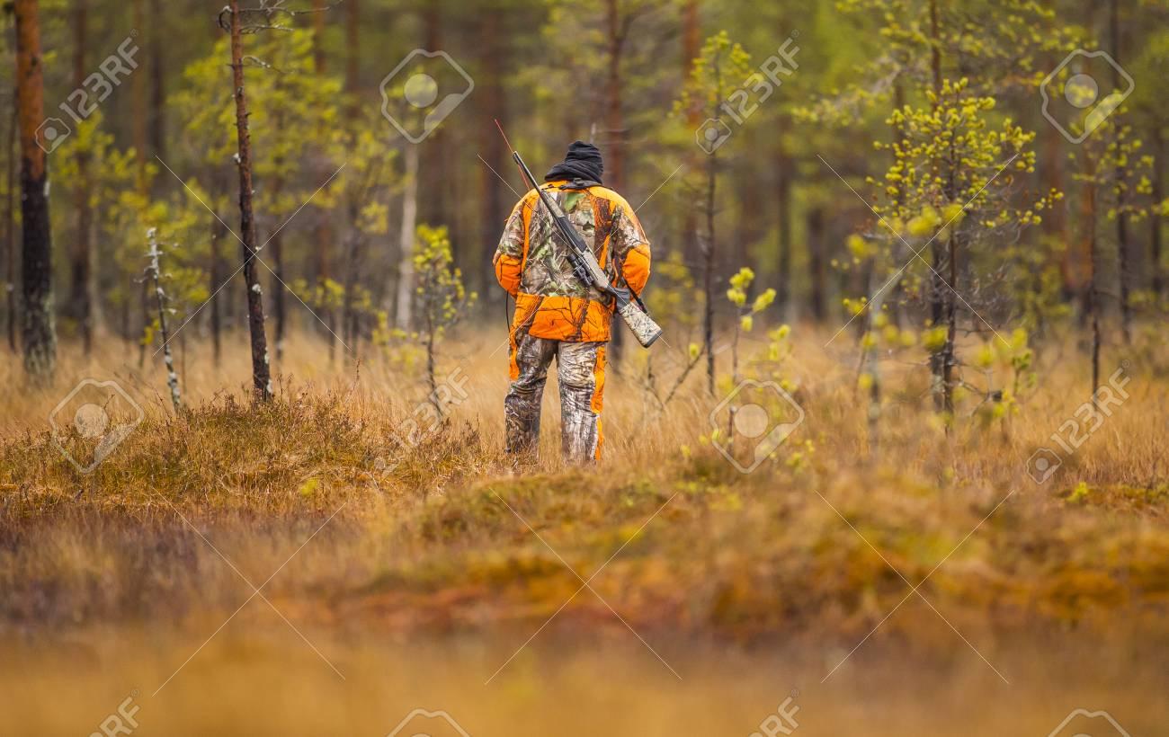 Hunter in the fall hunting season - 88115773