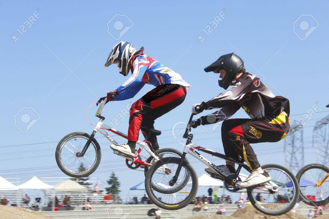 Two children jump a hill at a local BMX competition in Abbotsford, British Columbia on August 11, 2012.   Stock Photo - 14756991