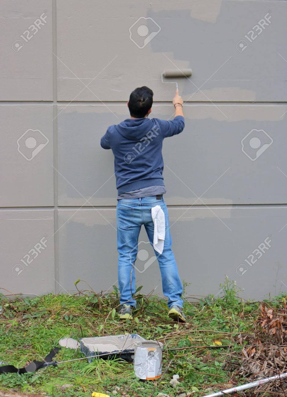 Un Peintre Industriel Applique Une Couche De Peinture Grise Sur Un Mur De Ciment Extérieur