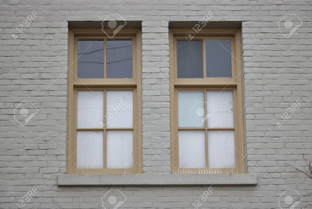 Encadrement De Fenetre Facade deux fenêtres extérieures à l'encadrement à l'ancienne montées sur une  façade en brique brune.