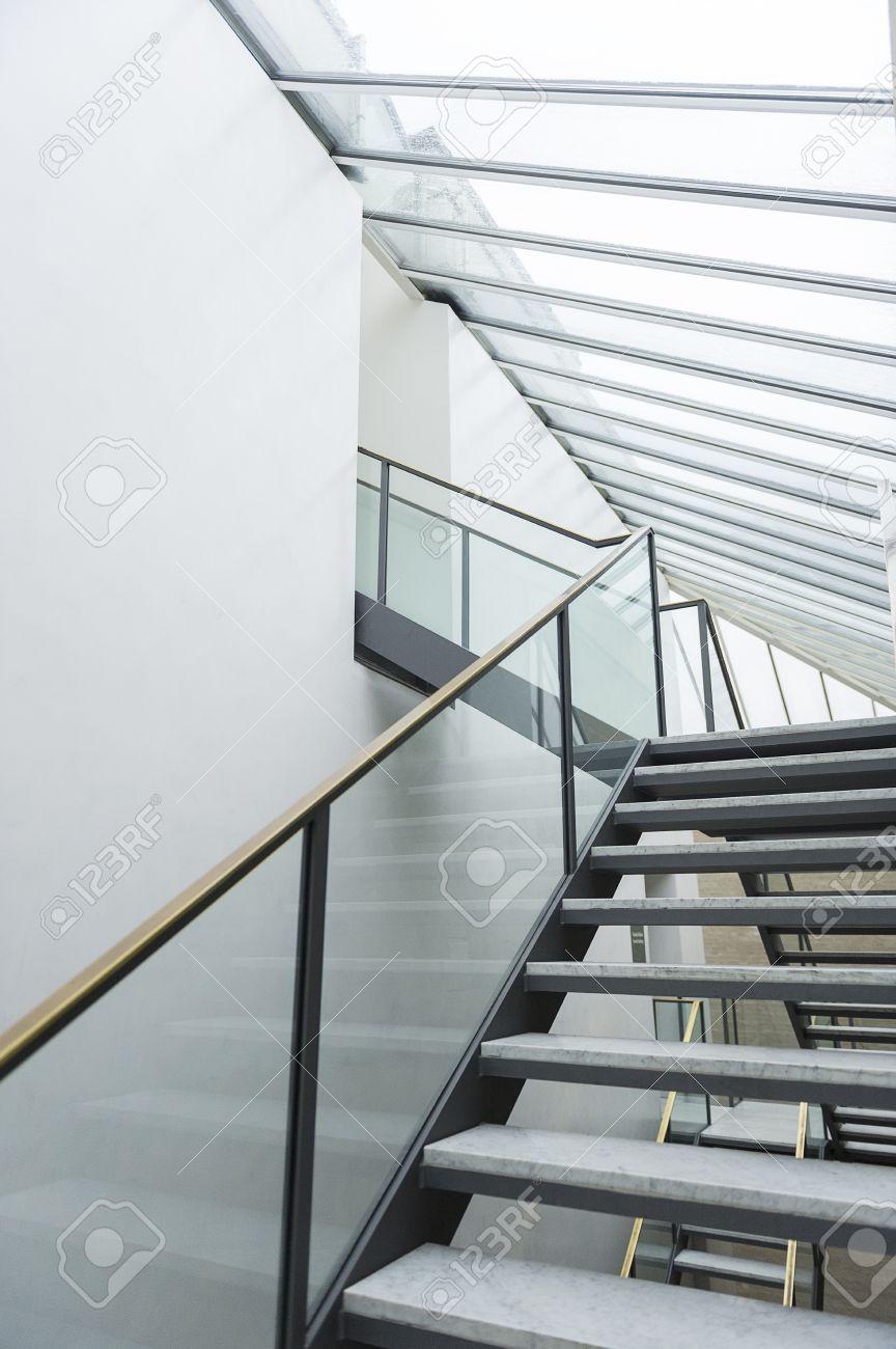 Ringhiera Scala Interna Moderna scala moderna con gradini aperti e una ringhiera di vetro che porta  attraverso più livelli per l'ingresso di una mansarda di un edificio  commerciale