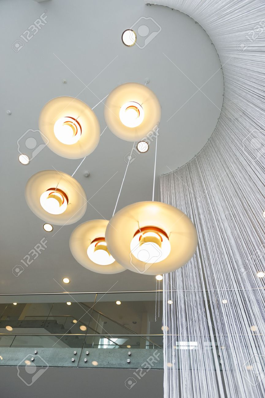 Modern overhead lighting fixture or chandelier consisting of five lights mounted in a hanging spiral at