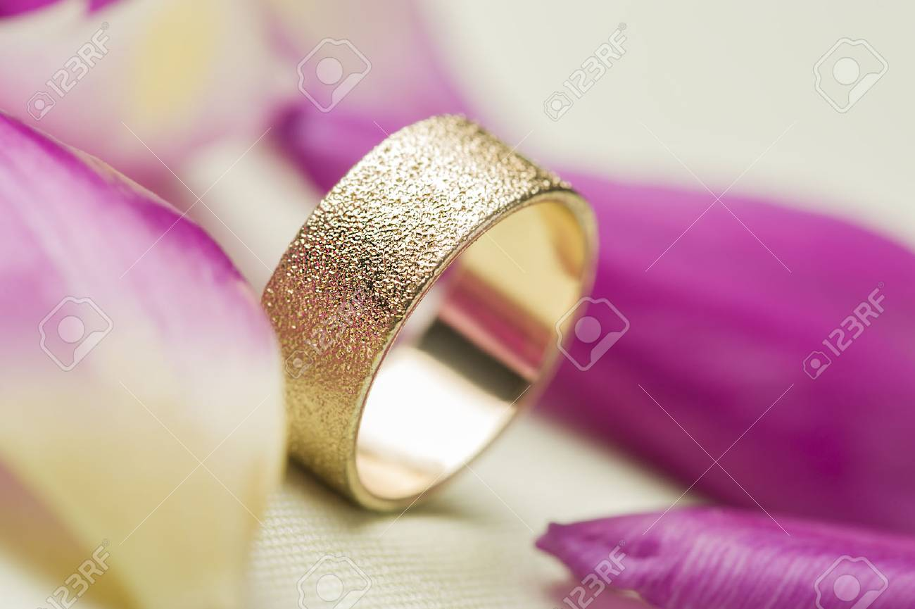 An Elegant Textured Gold Wedding Band Or Ring Standing Upright ...