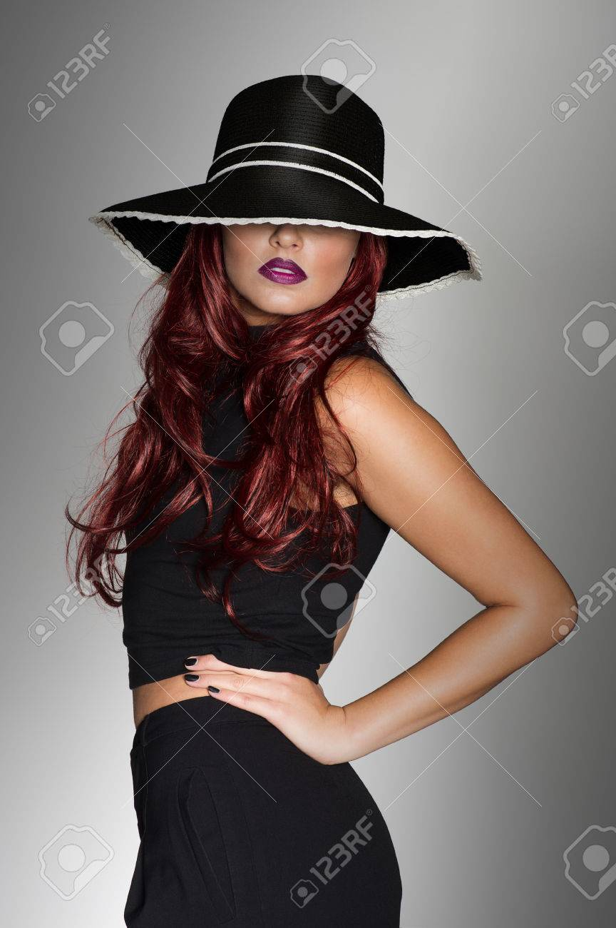 Elegant woman in a stylish black outfit and matching black hat seductively  covering her eyes posing 9c0d3e1500e