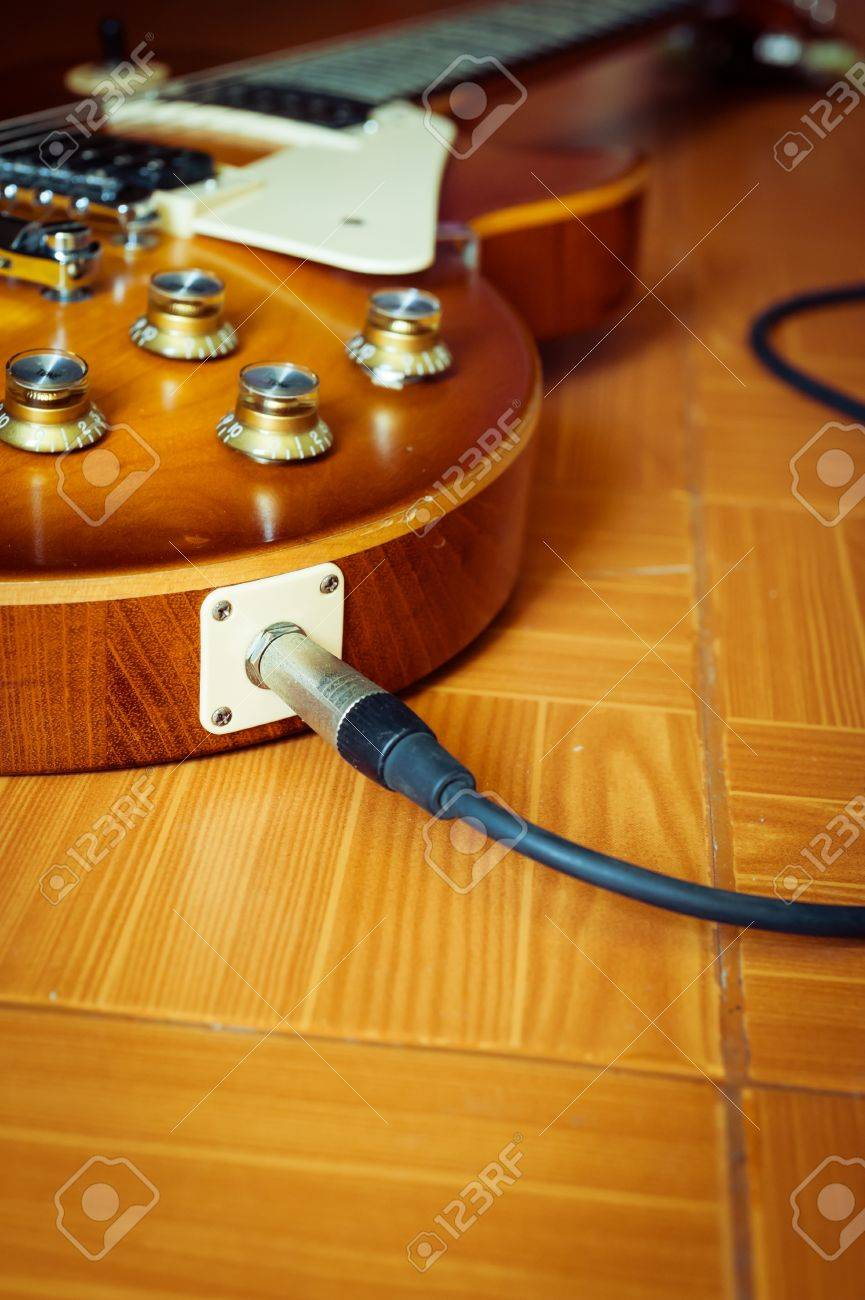 Electric guitar honey burst color on floor with jack cable Stock Photo - 14980627