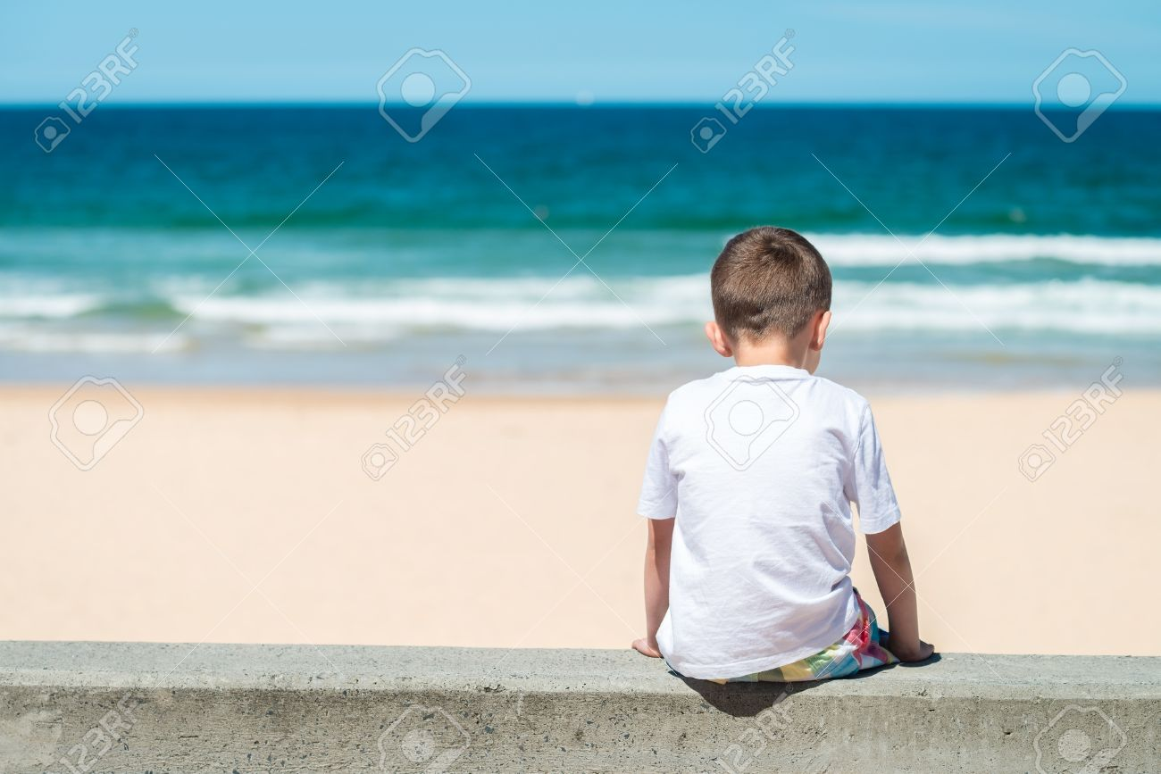 Sad boy sitting at he beach and thinking about something stock photo 54975764