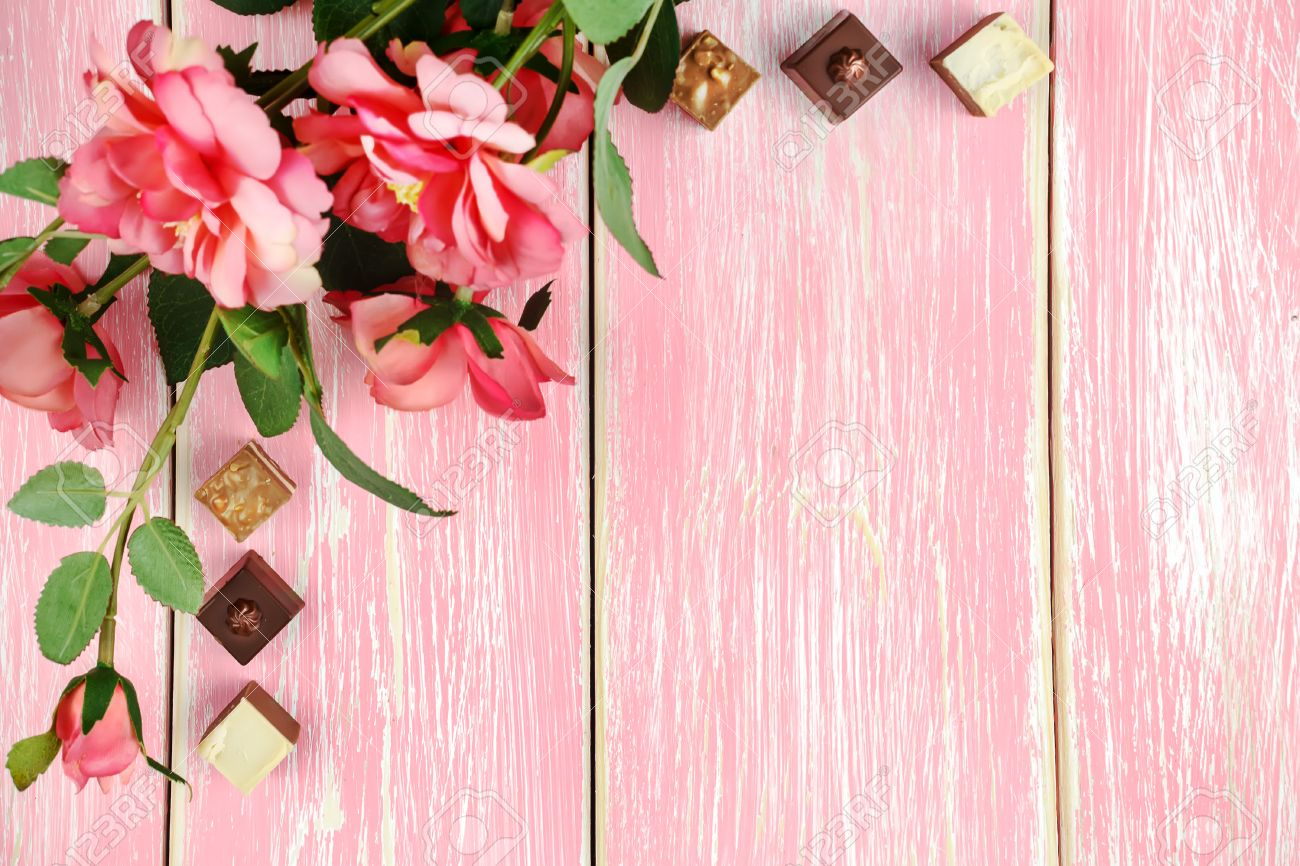 Copy Space Pink Wooden Background With Flowers And Candy Selective