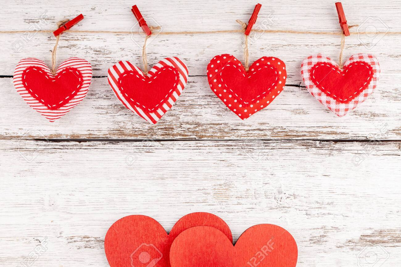 Valentines Background with Handmade Sewed Pillow Hearts Row Border with Red Pins on Jute Rope and Two Wooden Hearts at Rustic White Wood Background. Concept of Happy Valentine's Day. Copy Space - 138470333