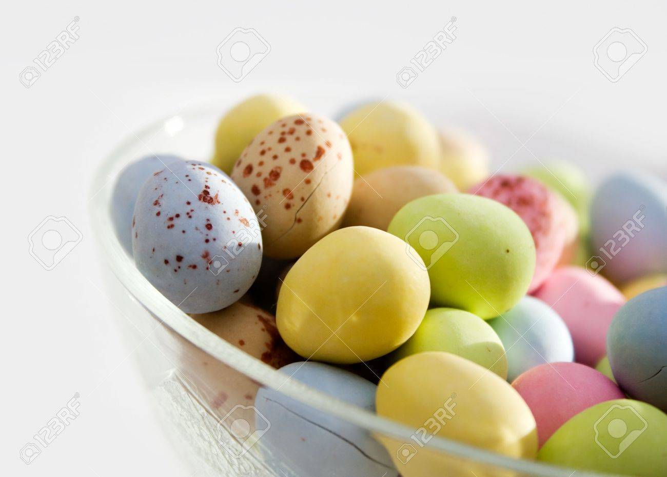 easter egg shape chocolate candy in glass bowl stock photo