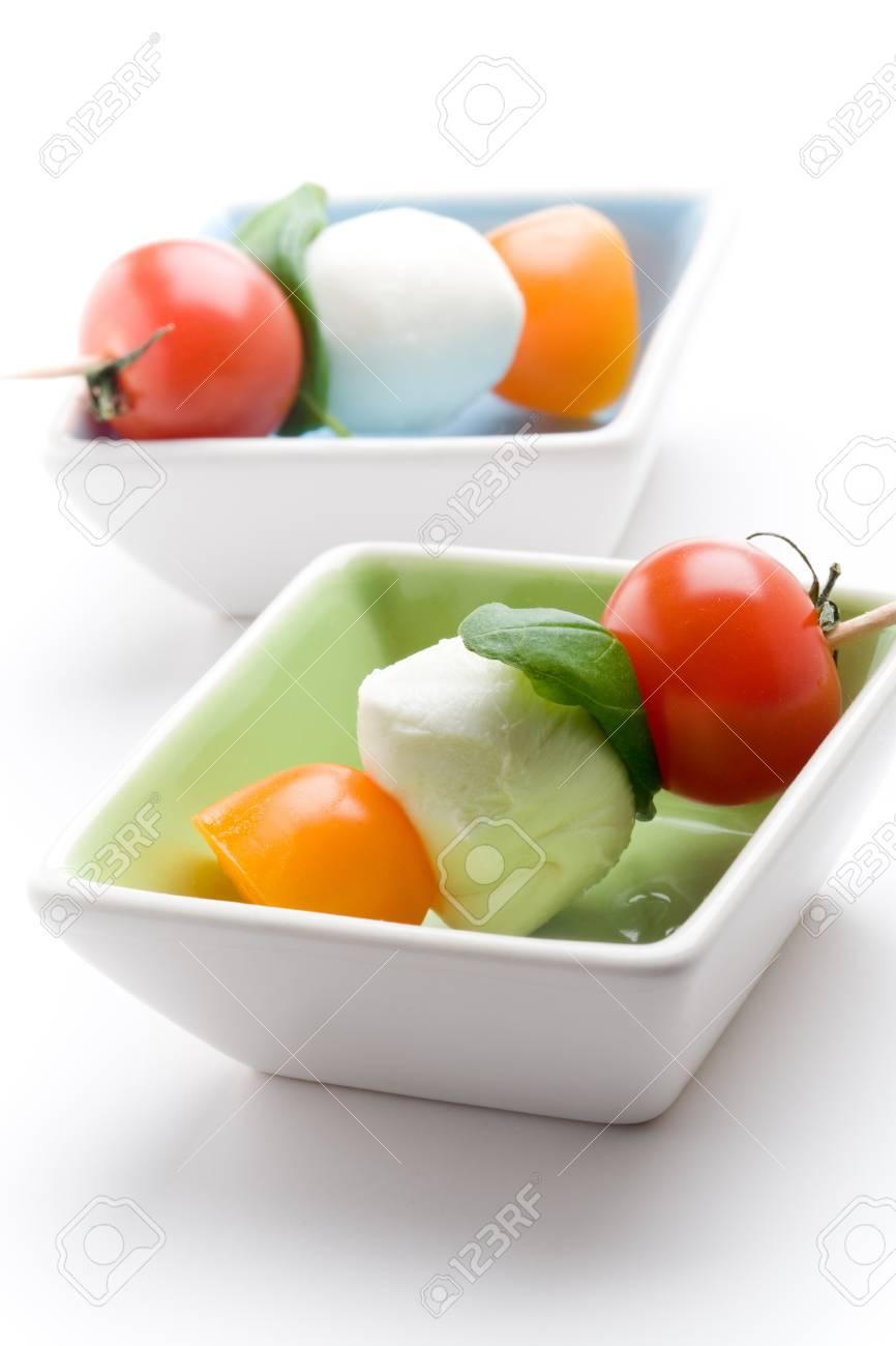 Mozzarella, tomatoes and fresh basil leaves on white background Stock Photo - 9069412