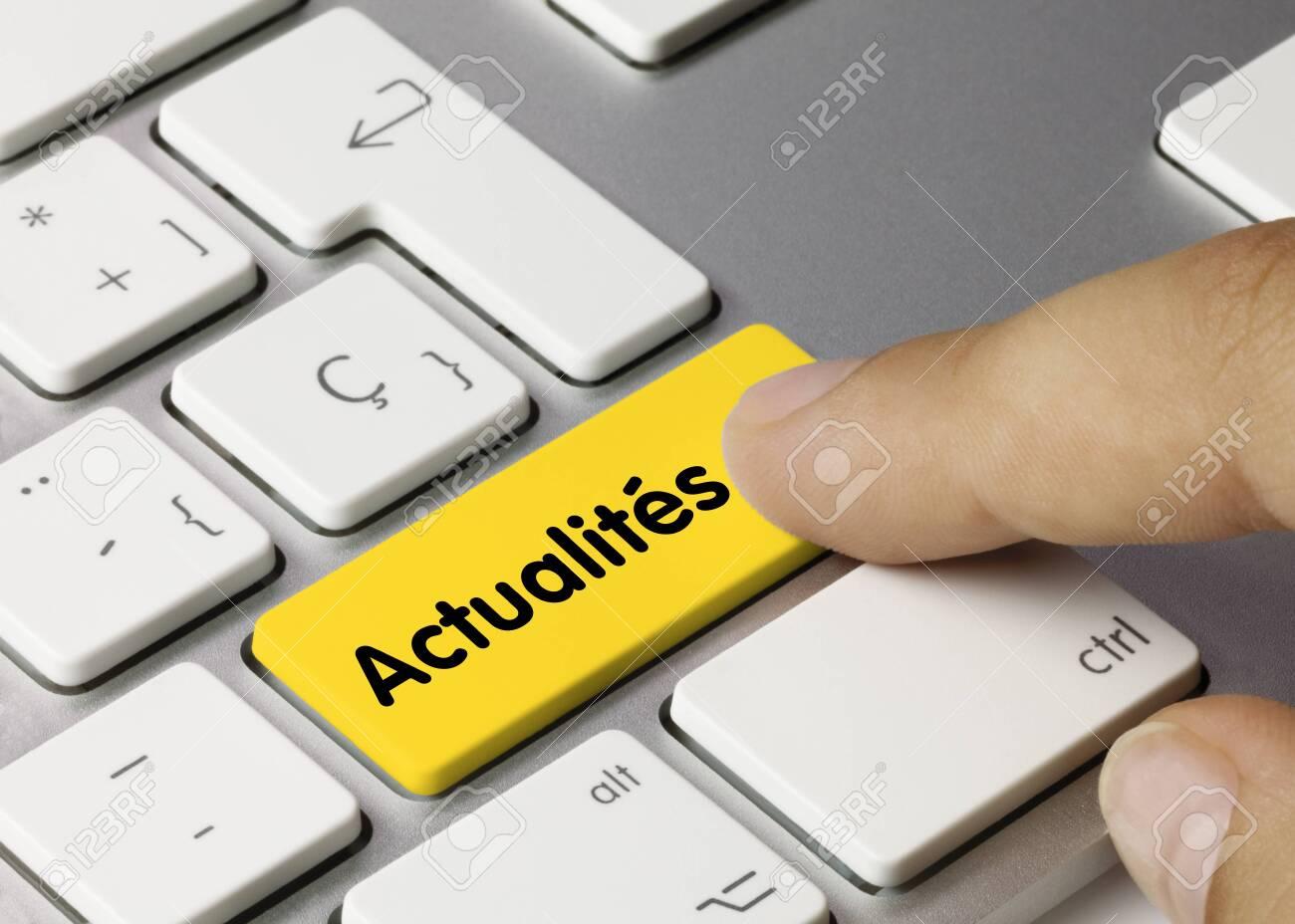Actualités Written on Yellow Key of Metallic Keyboard. Finger pressing key. - 147231351