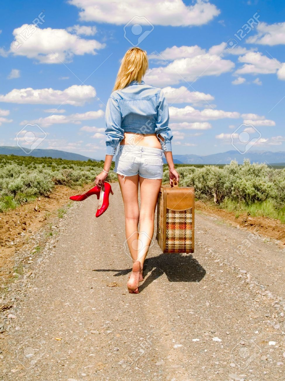 Girl walking on a dirt road barefoot with a suitcase carrying her red shoes Stock Photo - 5946510