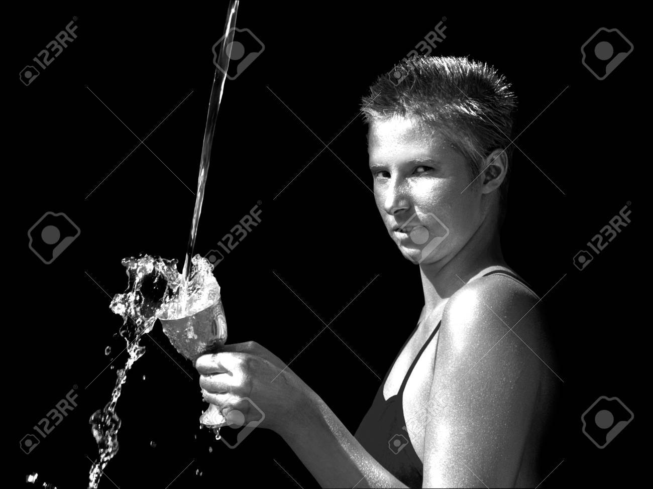 Androgynous young woman catching water in a goblet Stock Photo - 7315741