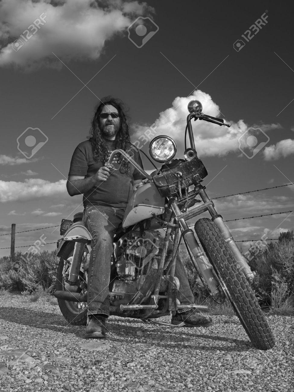 Une photo vous plait postez la ici..(Dans n'importe quel domaine) - Page 6 7315780-Aux-longs-cheveux-biker-sur-une-vieille-moto-classique-partiellement-maison-construite-American-Banque-d'images