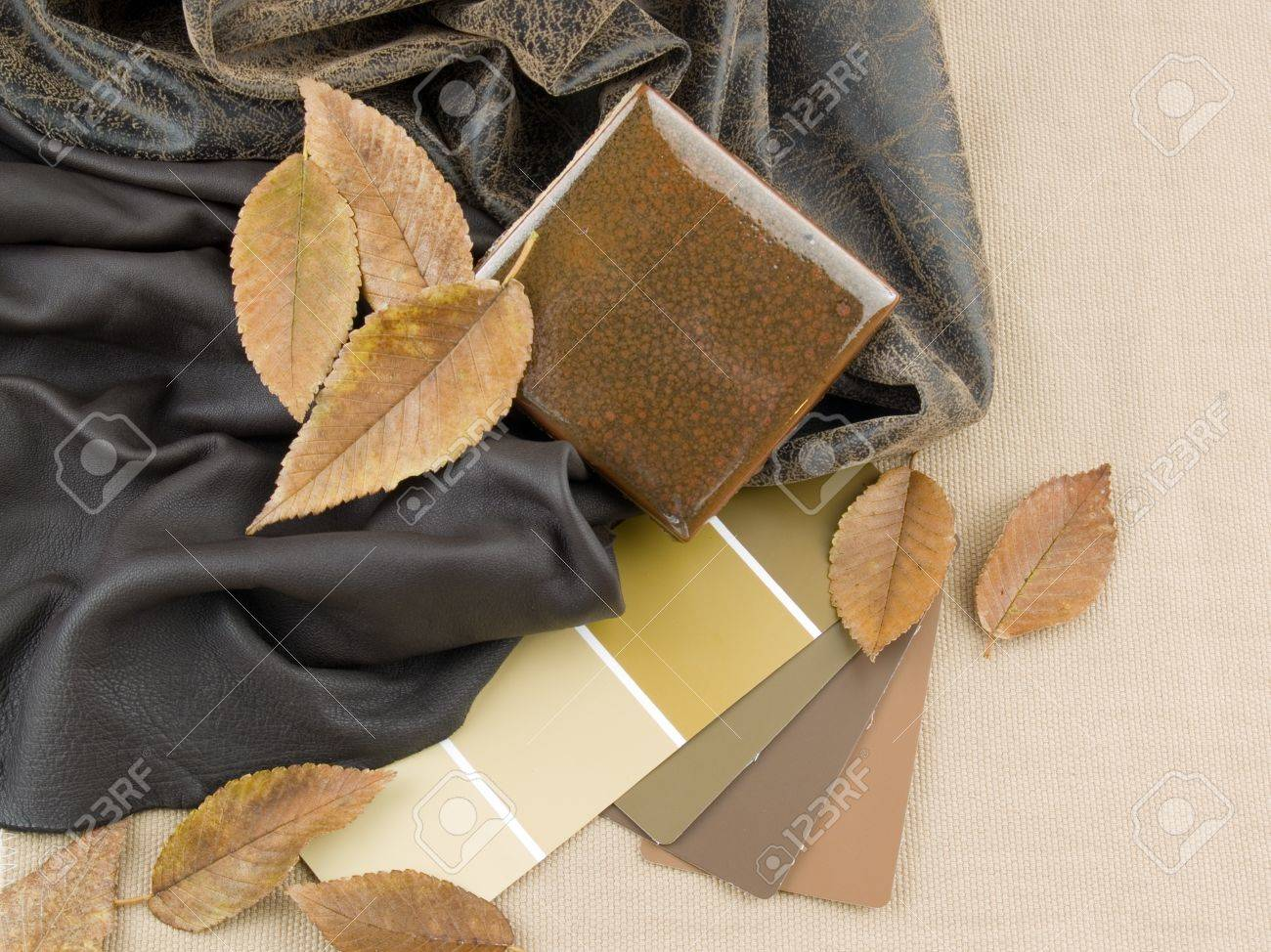 Earthy brownish interior design plan handcrafted ceramic tile with two brownish leather samples and paint