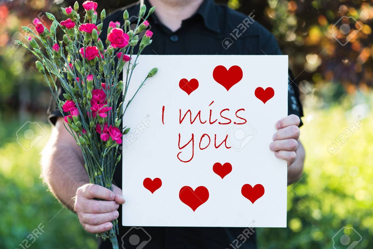 Man Holding Flowers And Board I Miss You Stock Photo Picture And