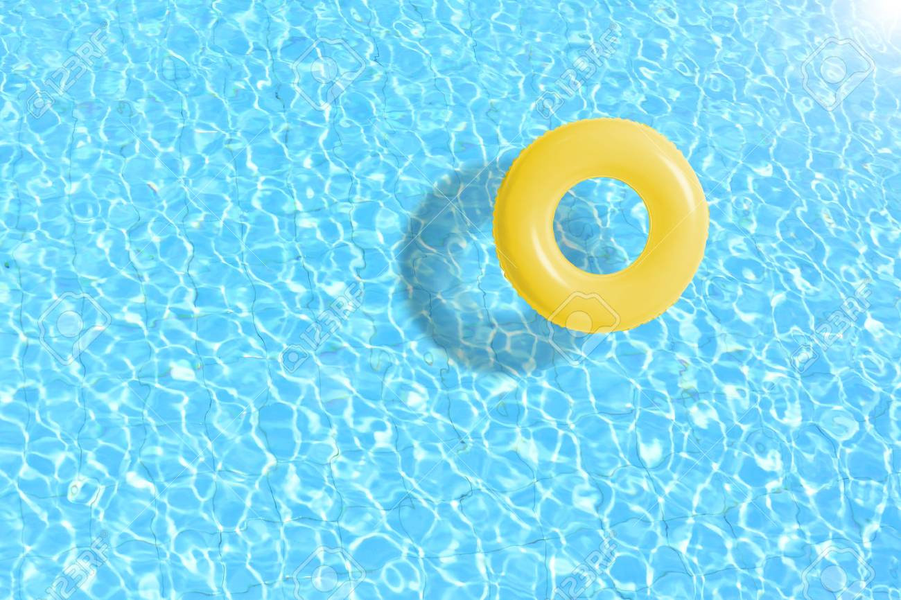 yellow swimming pool ring float in blue water. concept color..