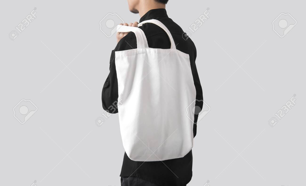 158dc68f Man is holding bag canvas fabric for mockup blank template isolated on gray  background. Stock