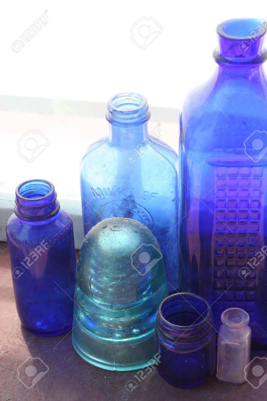 antique vintage blue glass bottles on windowsill in natural light