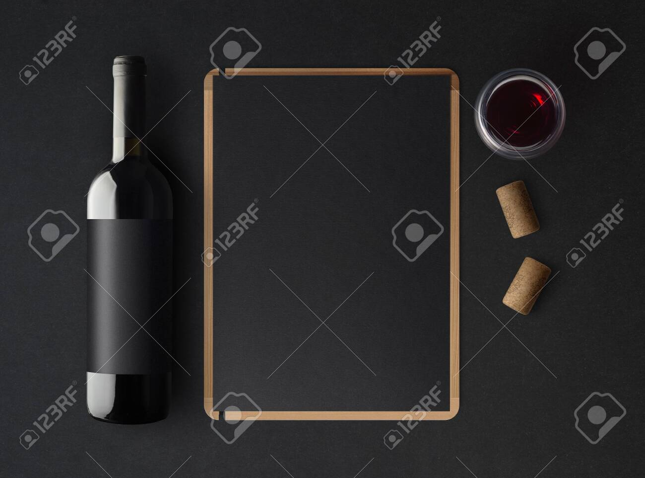 Bottle of red wine with a black label on a dark background, a wine menu template and a glass of wine. Mockup. Top view. - 149691723