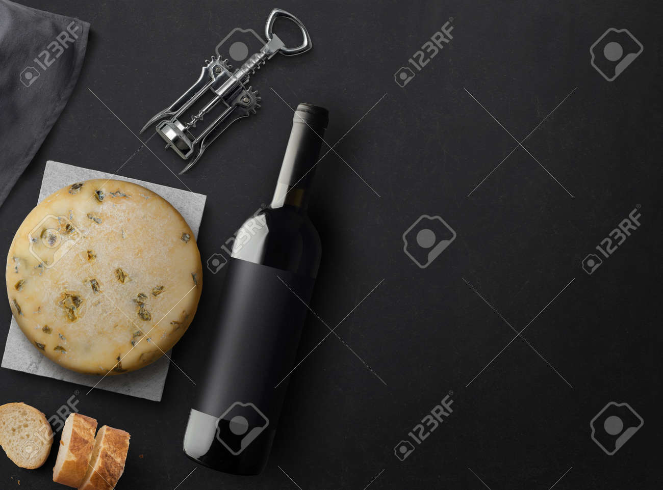 Red Wine bottle, corkscrew, cheese, wineglass, bread on black stone background, top view, copy space. Wine bottle mockup. Top view. 3d illustration. - 150522555