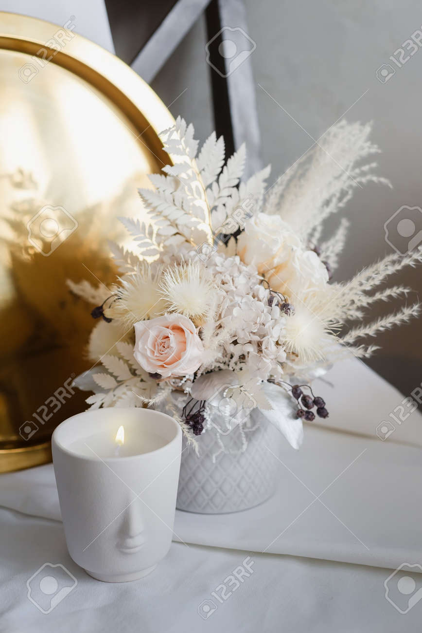 Stylish composition of preserved flowers and dried flowers in a light color scheme on the background of a golden tray with a burning candle. Photo of a bouquet with roses in the interior. - 170743101