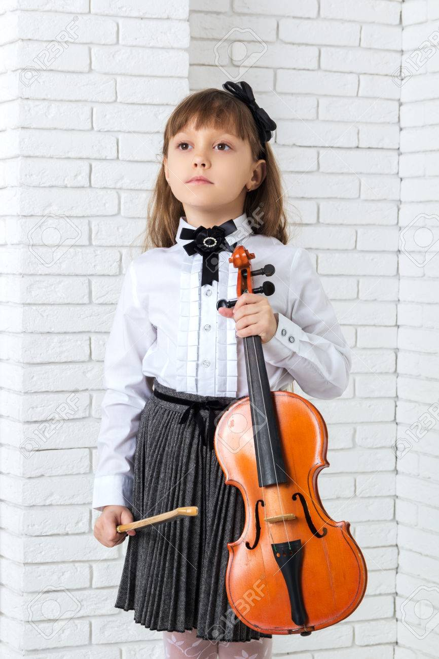 Little girl standing and holding fiddle, looking away - 56544517