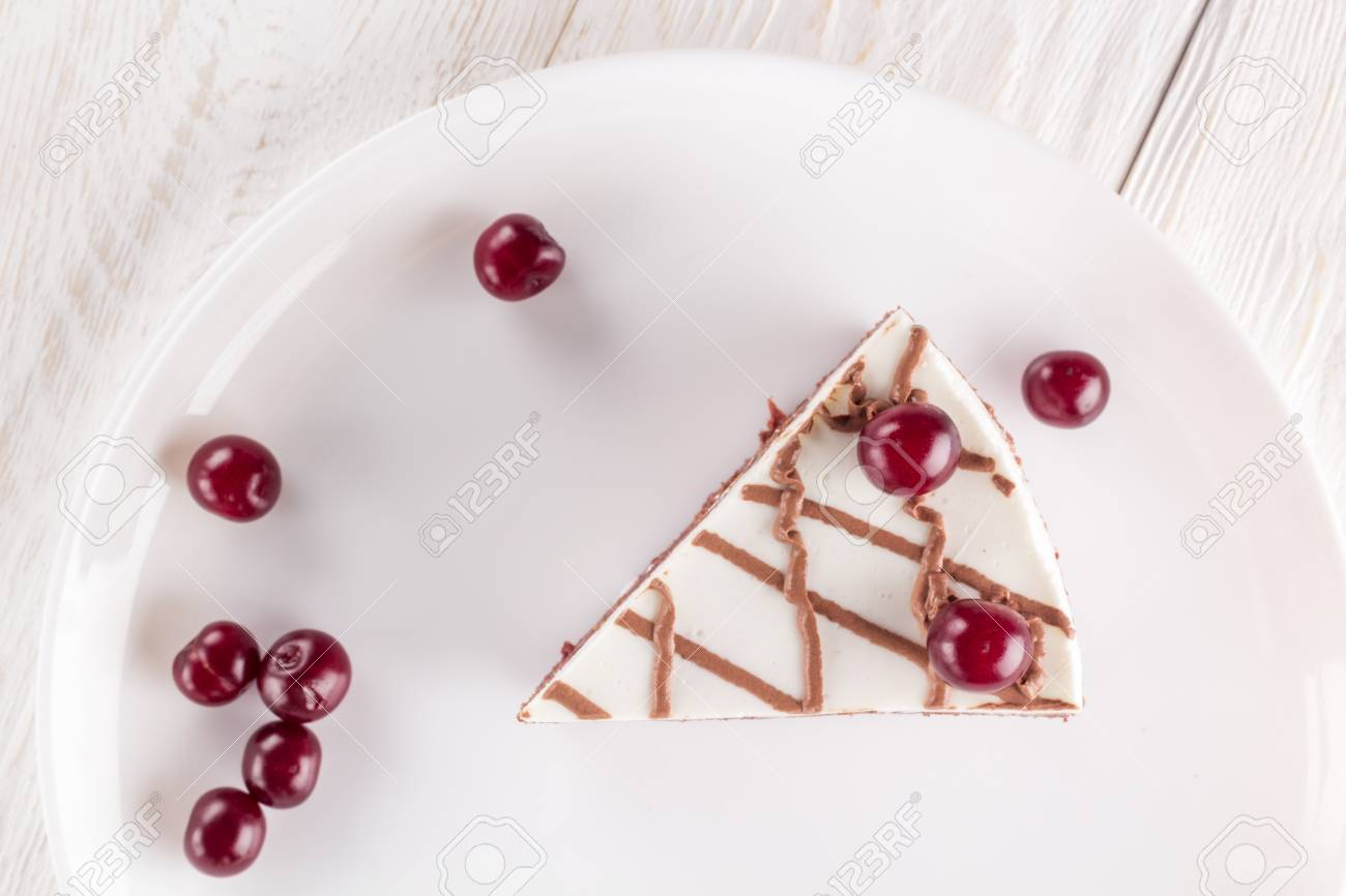 Piece of chocolate cake on plate decorated cherries and chocolate - 98555850