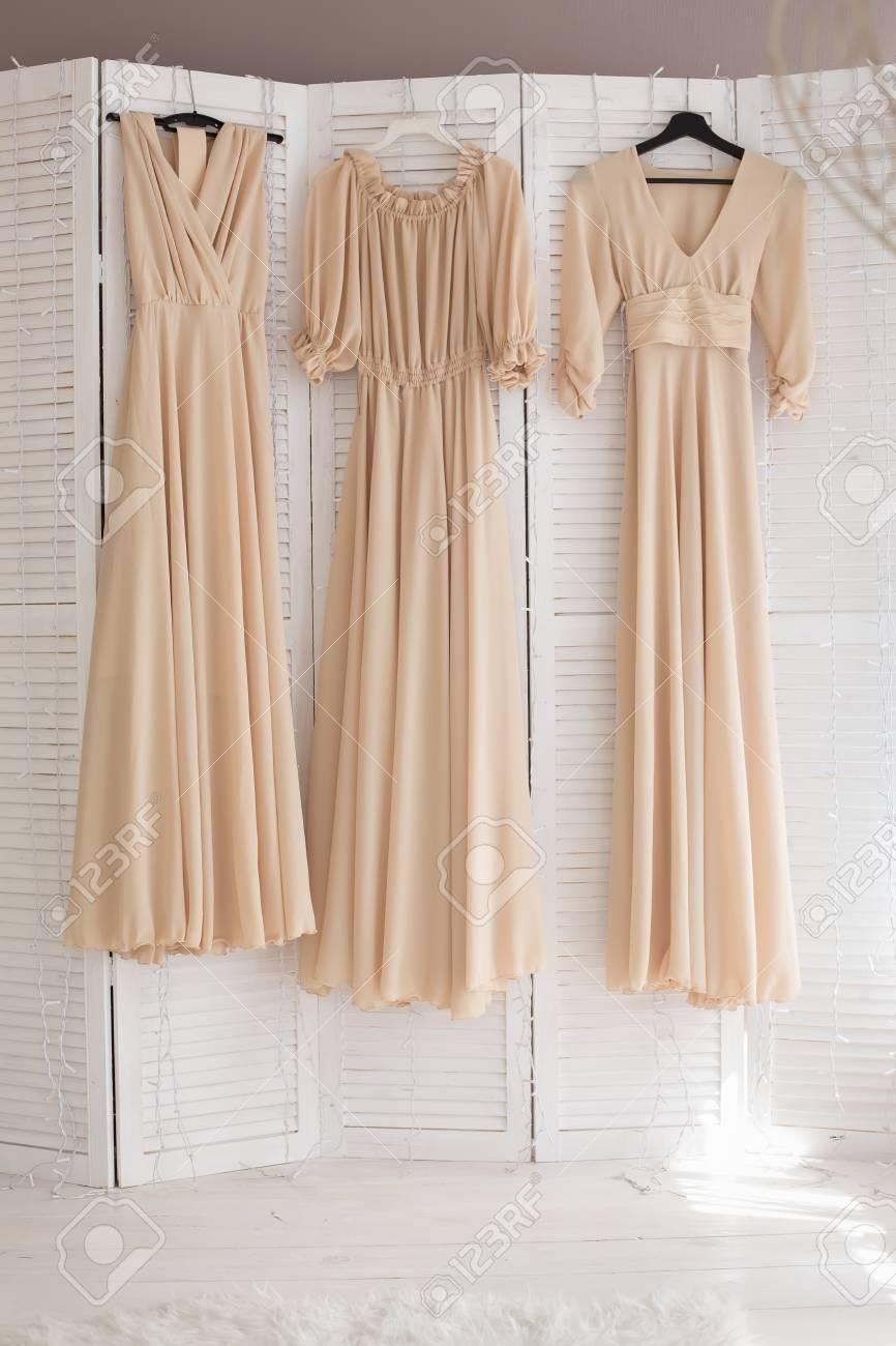 Tres Vestidos De Damas De Honor De Color Beige Para Colgar En Perchas En La Habitación