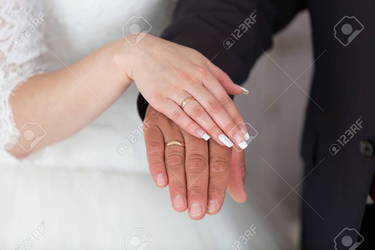 Gold Wedding Rings On The Hands Of The Newlyweds Stock Photo