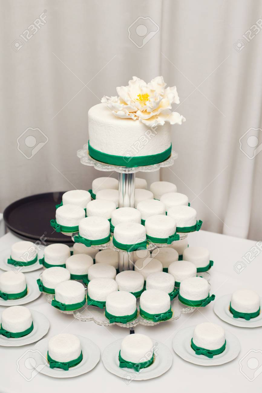 White Wedding Cake With Green Details And Cupcakes Stock Photo