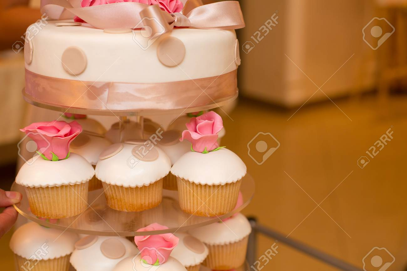 White Wedding Cake And Pink Flowers And Cupcakes Stock Photo