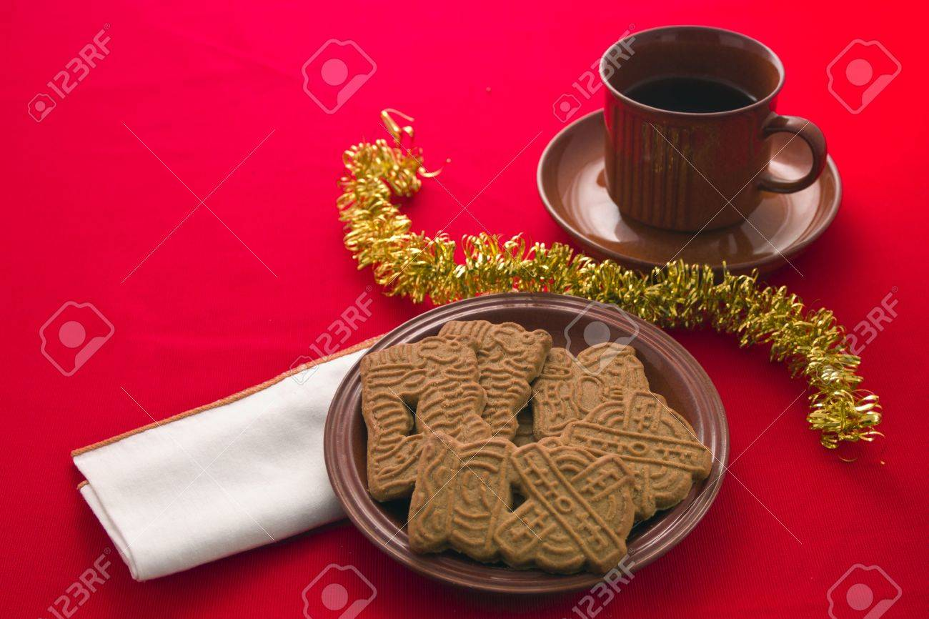 Spiced Christmas Biscuits With Drink In Cup And Saucer On Red