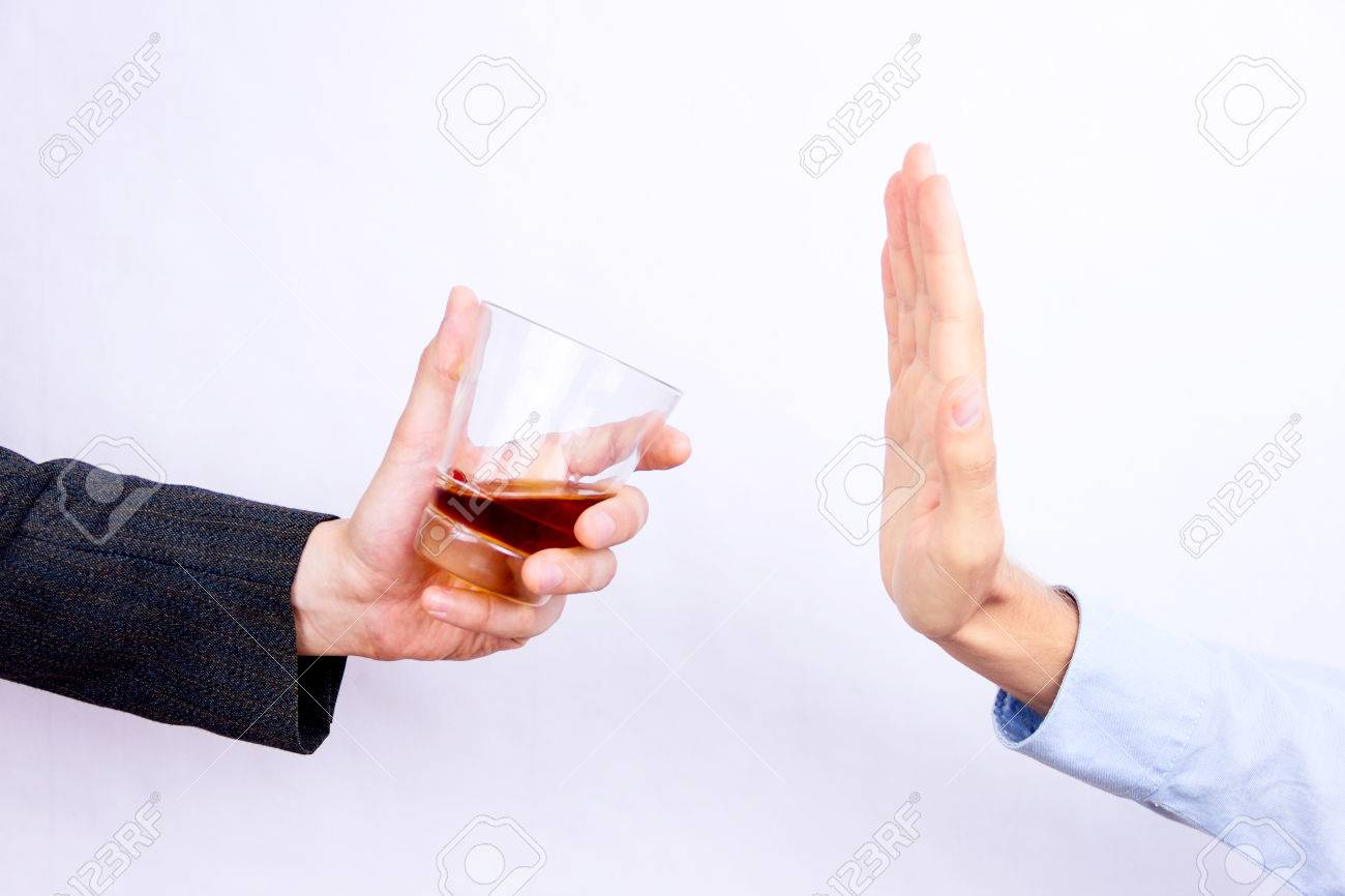 Close-up of businessman hand rejecting glass of whisky offered by businessperson - 70943896