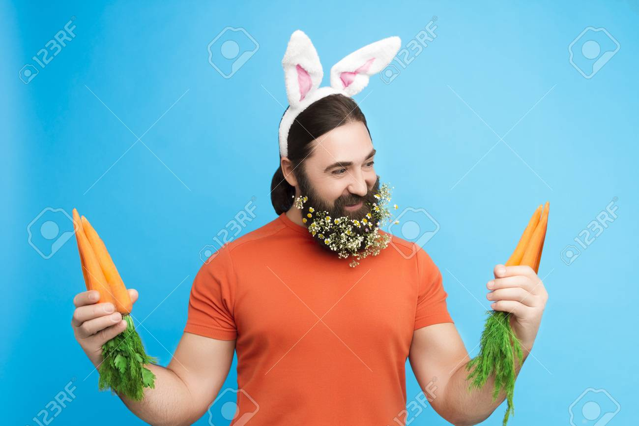 Nice kind muscle man male with spring's flower's beard, white ears of rabbit, carrots in orange t-shirt isolated on blue background - 94907764