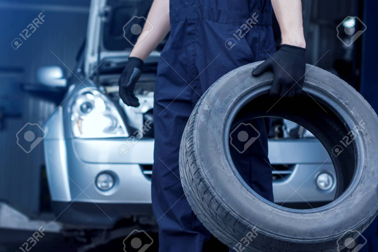 Mechanic in blue jumpsuit is repairing car at service station. Closeup of repairman hands are holding tyre from wheel in workshop. Vehicle with open hood on background. Tire fitting concept. - 127904703