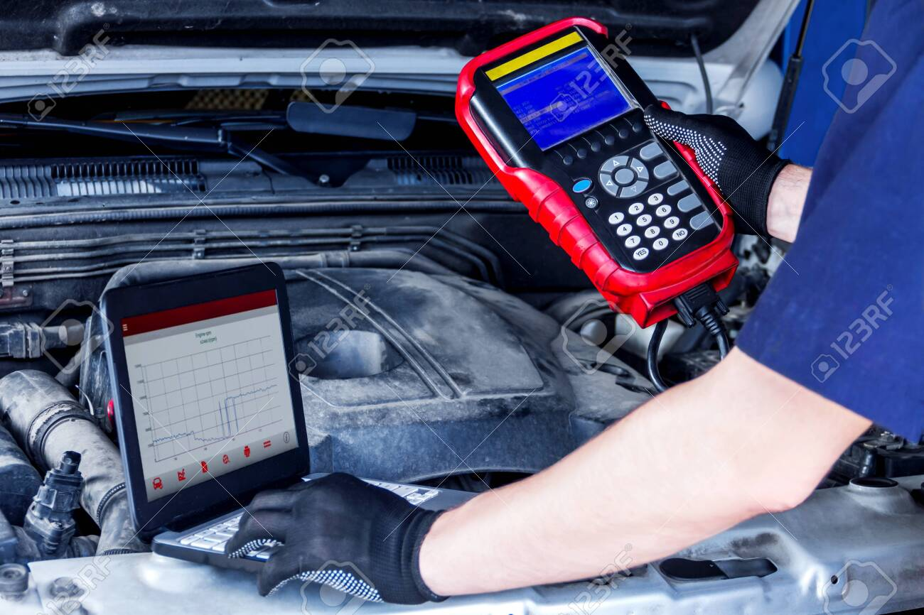 Closeup laptop screen with special software, equipment at vehicle with open hood. Repairman is conducting diagnostics and detecting problems at workshop. Mechanic is repairing car at service station. - 127904959