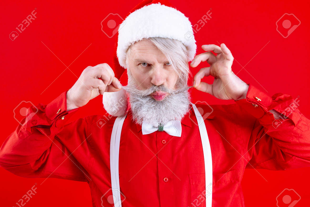 Positive modern Santa Claus, wearing stylish red hat, shirt and white suspenders. Happy, old man with long white beard holding his mustache and grimace. Winter holidays, new year celebration concept. - 159830228
